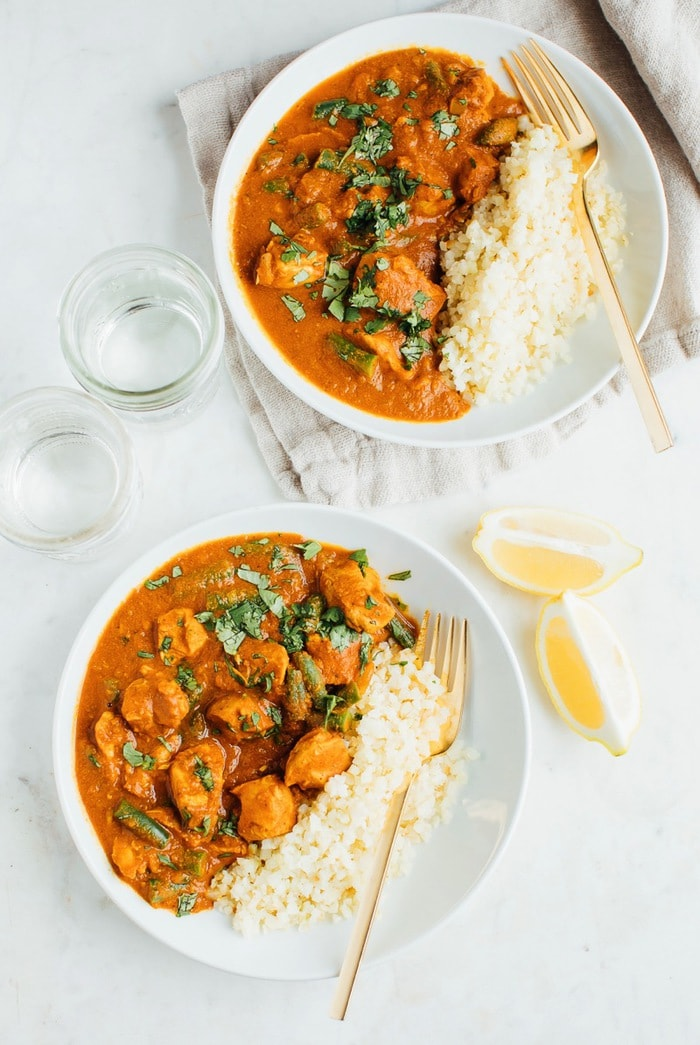 Dairy-free butter chicken with cauliflower rice served in two white bowls.