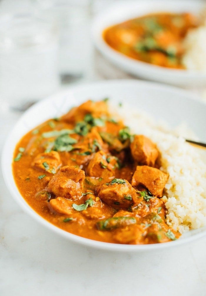 Dairy-free butter chicken in a white bowl served with cauliflower rice.