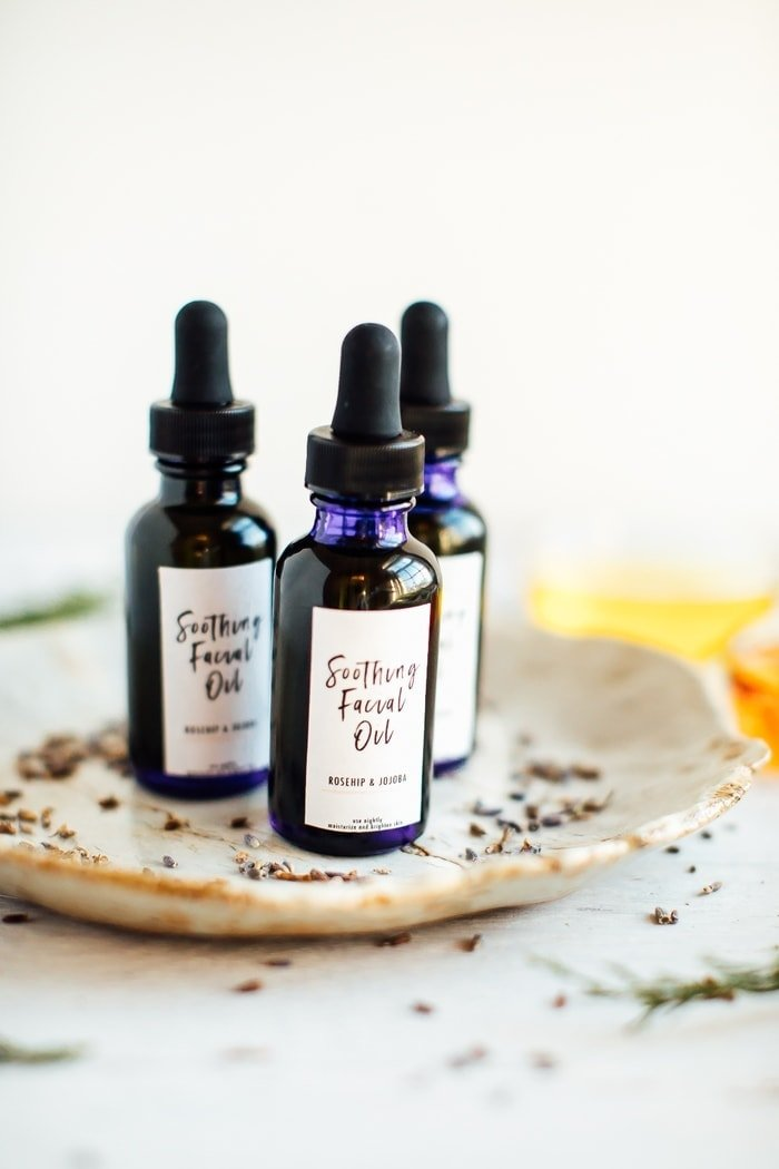 3 bottles of DIY facial oil on white tray with dried lavender buds.