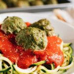 Turkey meatballs over zucchini noodles topped with tomato sauce.