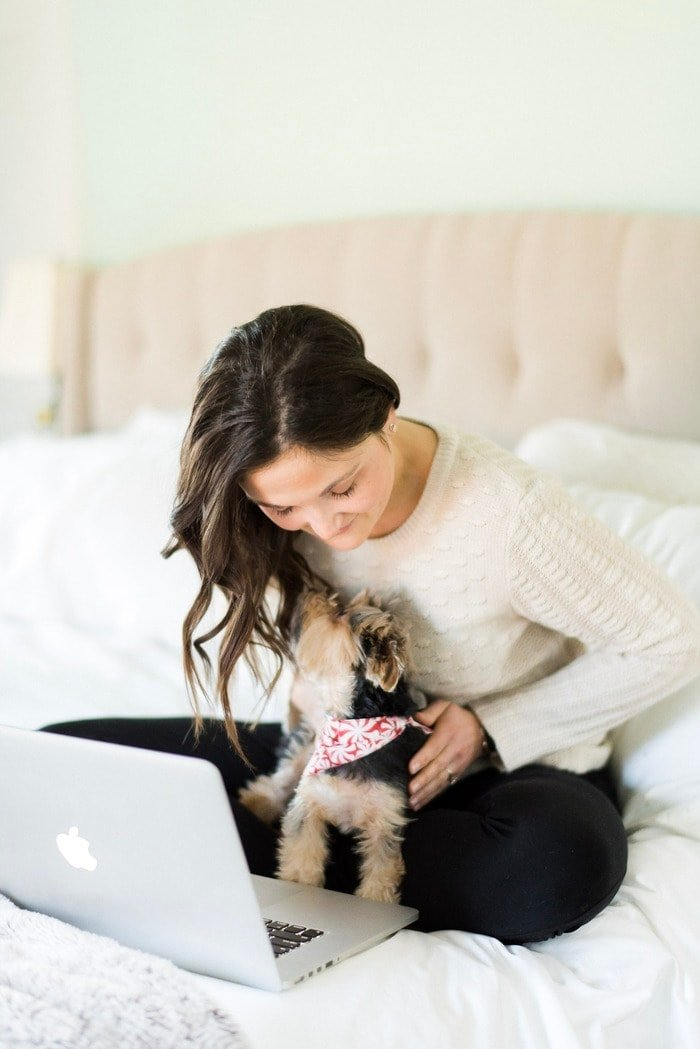 Woman sitting on her bed working from her laptop with her dog.