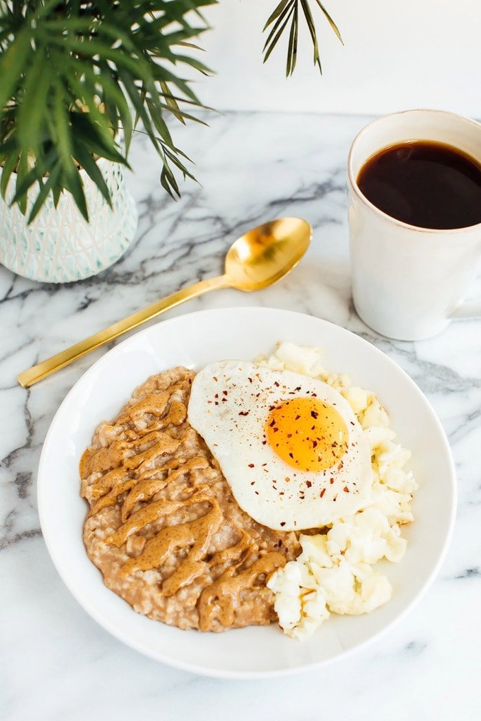 Sweet + Savory Egg and Oatmeal Combo Bowl in a white bowl served with gold spoon and cup of coffee.