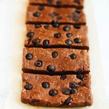 Peanut butter chocolate protein bars with chocolate chips in a row on a white textured surface.