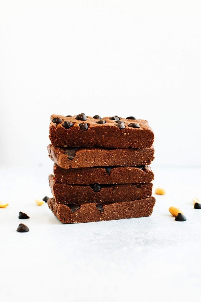 Stack of peanut butter chocolate protein bars with chocolate chips on a white textured surface.