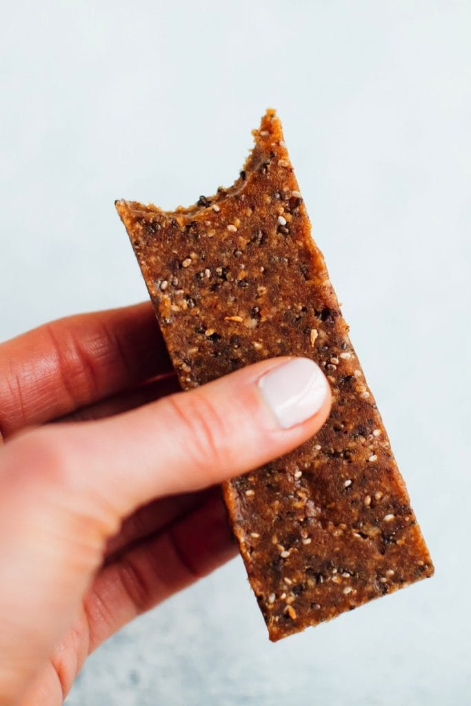 Hand holding a chia bar with bite taken out of it.