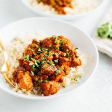 Tempeh tikka masala with chickpeas on cauliflower rice on a white plate.