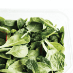 """Container of salad greens with text """"how to keep greens fresh longer"""""""