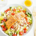 Salmon over Mediterranean salad in a white bowl with a fork and dressing on the side.