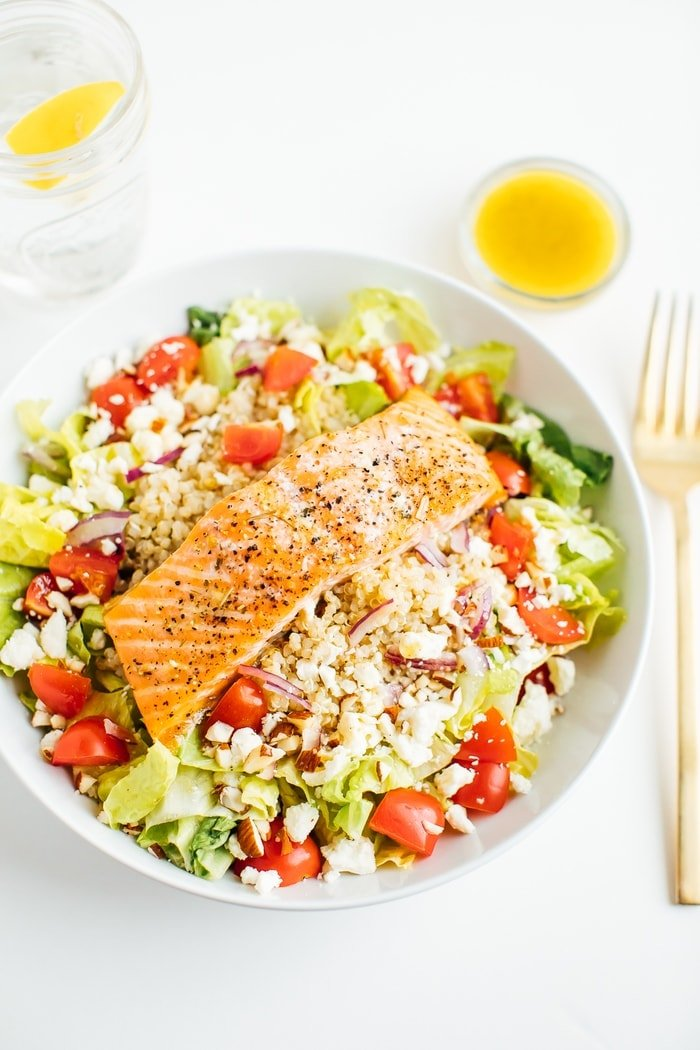 Mediterranean Salmon Salad with quinoa, grape tomatoes, almonds, feta, red onion and romaine lettuce. Dressing and water with lemon on the side.