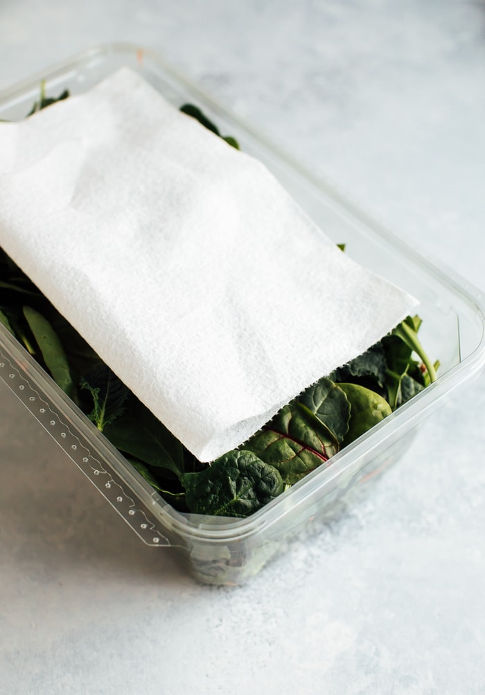 Plastic clam-shell container with baby greens and a paper towel on top.