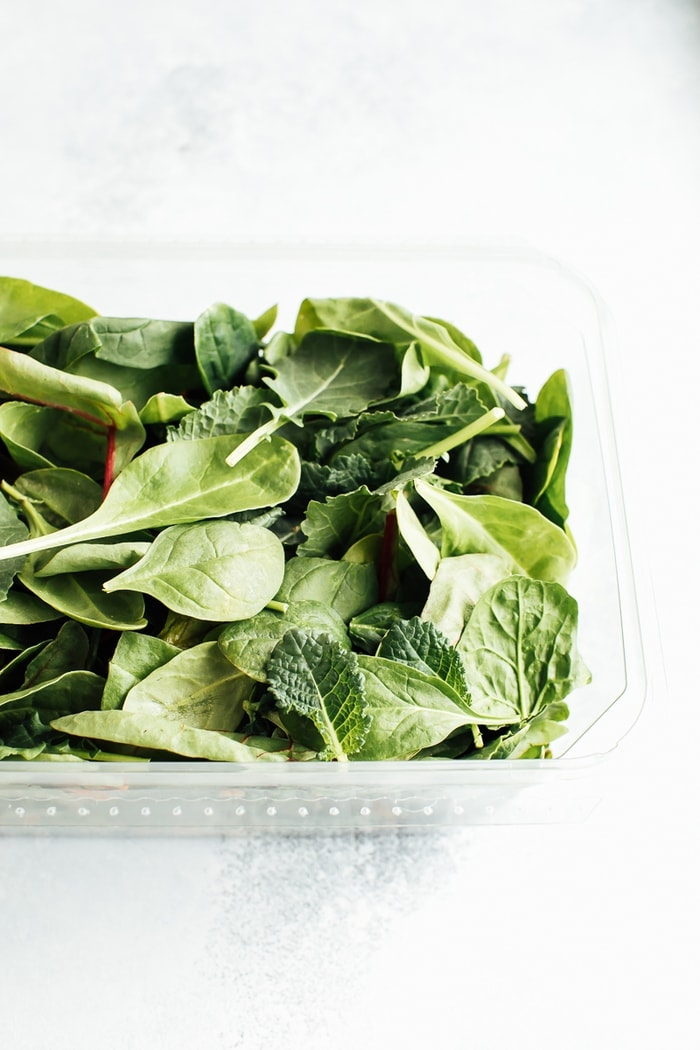 A plastic clam-shell container with baby greens.