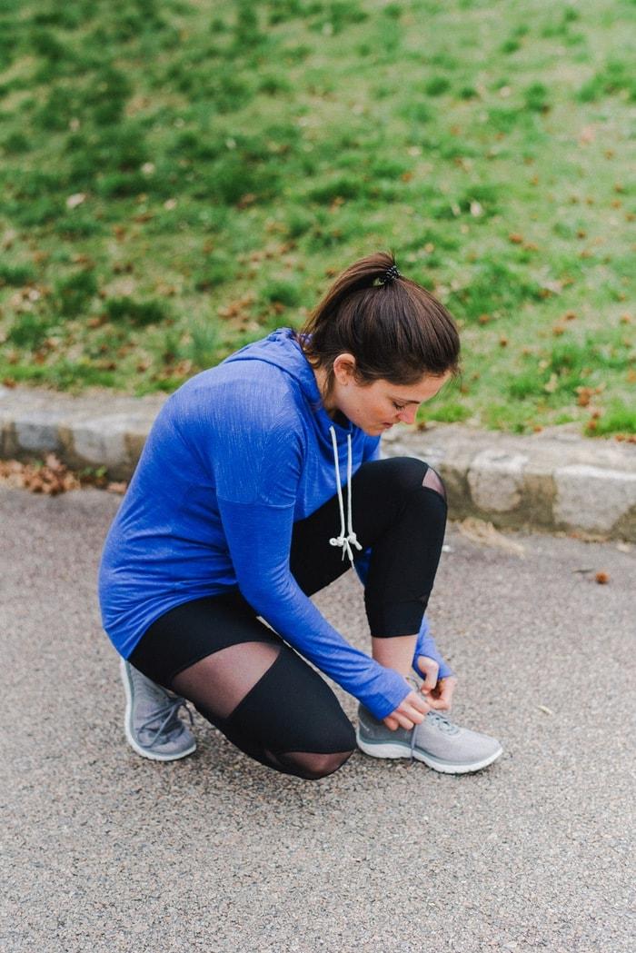 Woman wearing workout gear tying shoe