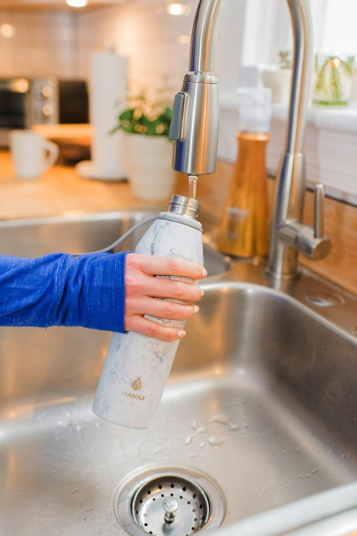 Filling up a marble water bottle with water from the sink.