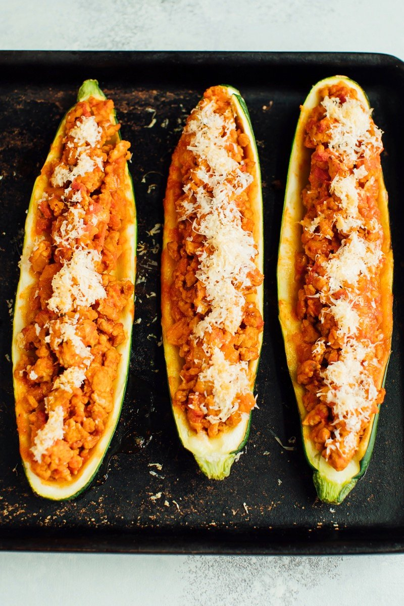 Three zucchini boats on a baking stone with turkey and parmesan on top.