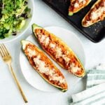 Two healthy zucchini boats on a plate with a baking stone and salad.