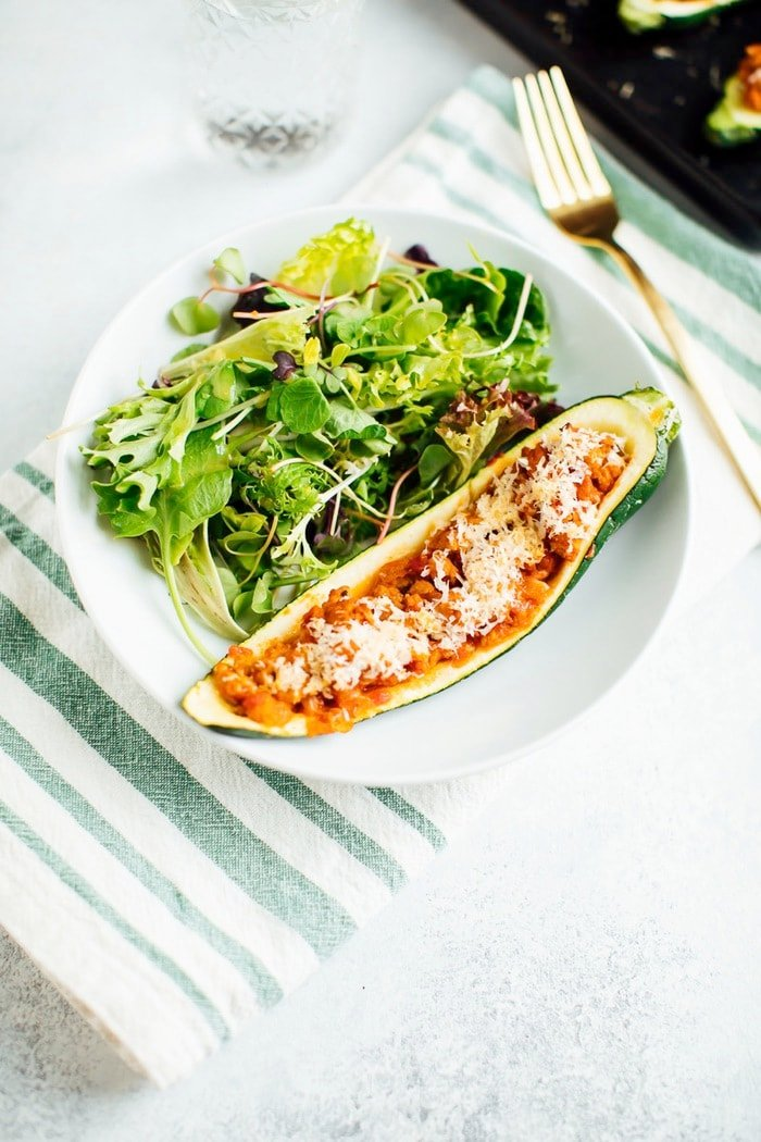 One turkey zucchini boat on a plate with salad.