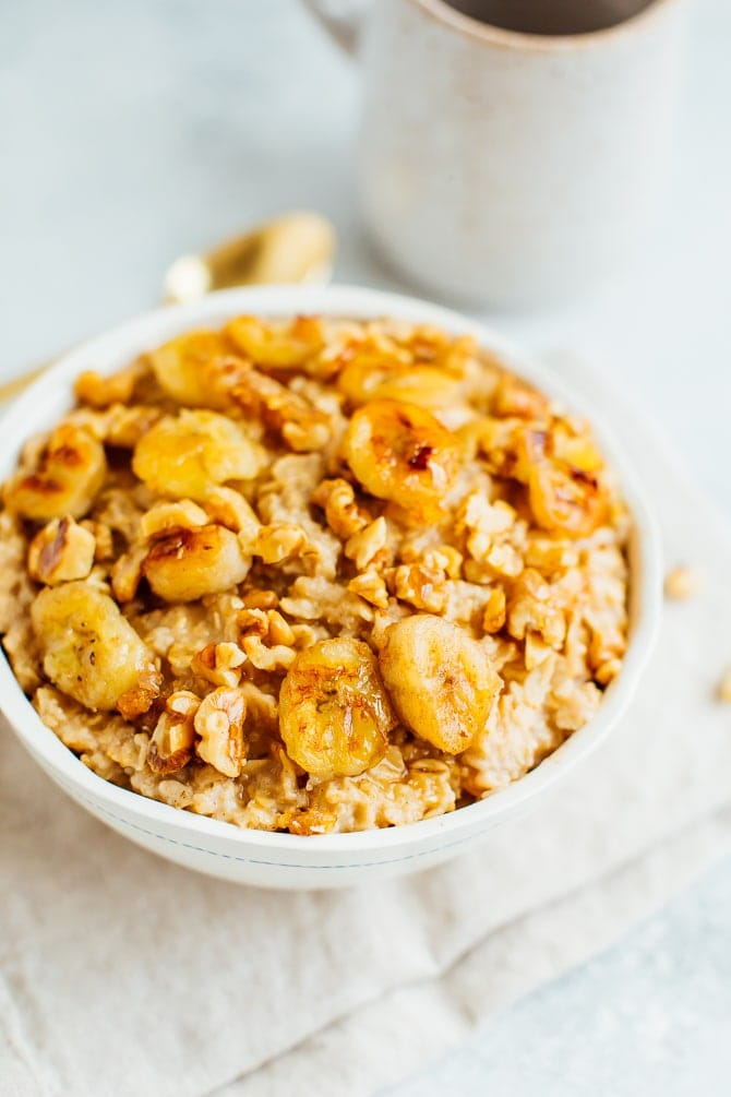 Banana bread oatmeal in a white bowl with caramelized bananas and toasted walnuts on top. Gold spoon and coffee mug in the background.