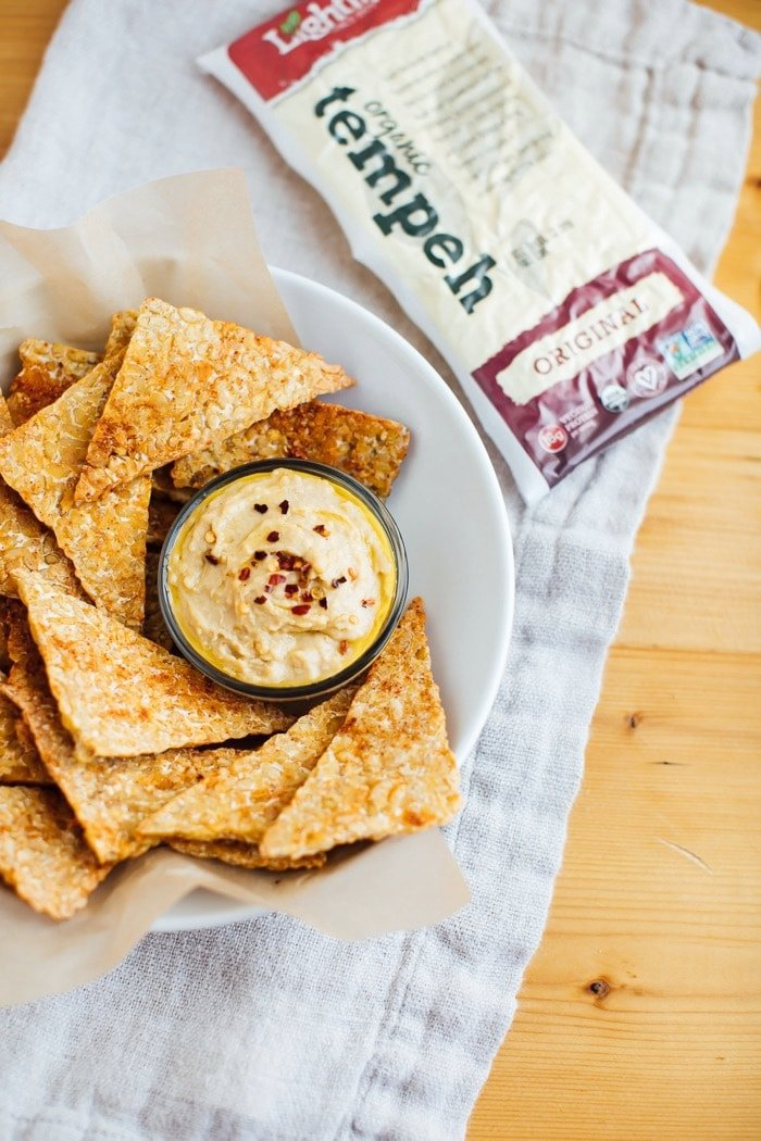 Close up of BBQ tempeh chips with hummus in a white bowl with brown parchment paper. Package of Lightlife tempeh in the background.
