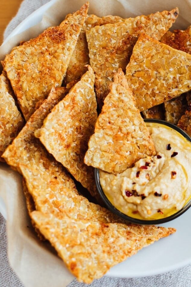 Baked bbq tempeh chips in a white bowl with hummus.