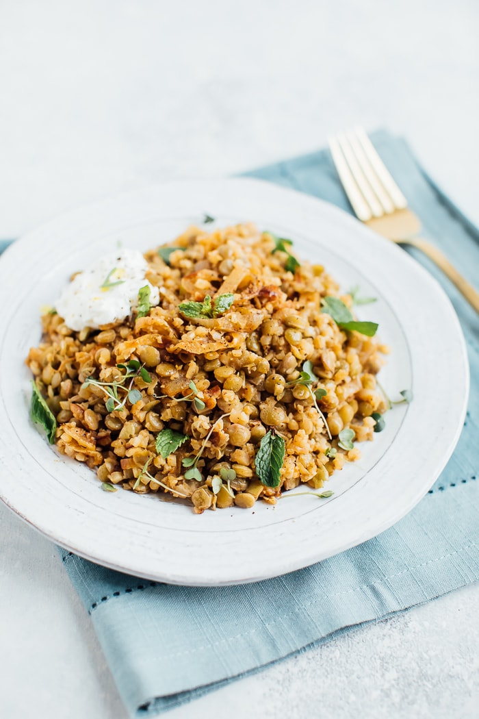 Caramelized onions, lentils and cauliflower rice on a rustic plate with a gold fork in the background.