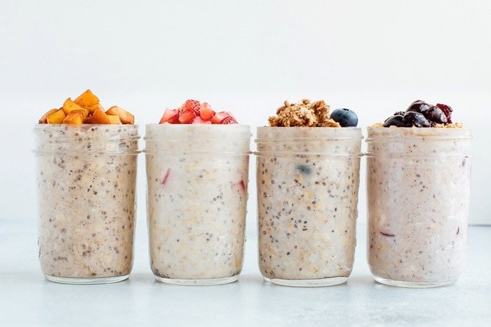 Overnight oats in pint-size mason jars with fruit on top.