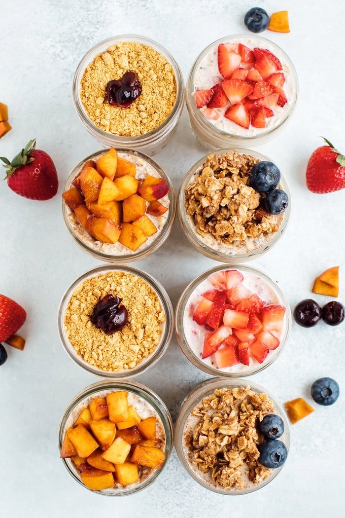 8 jars of overnight oats with fruit and toppings.