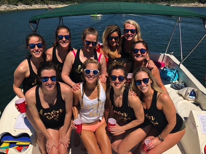 10 women smiling while on a boat, wearing matching tank tops.
