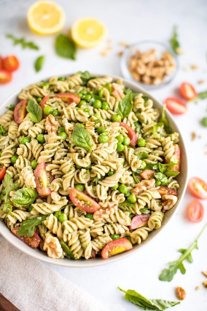 bowl of vegan pesto pasta salad with basil, peas and tomatoes