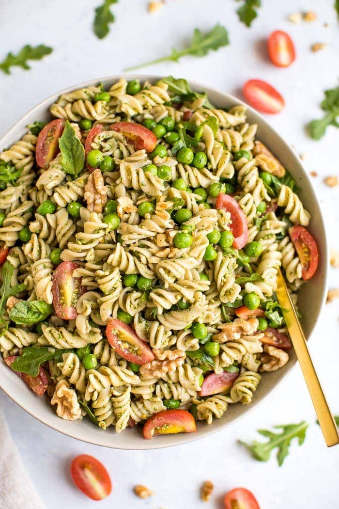 Walnut pesto pasta salad in a large bowl with gold spoon and veggies around the bowl.