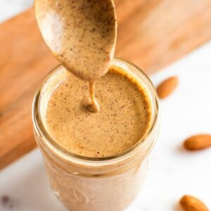 Spoon dipping into almond dressing in a jar.