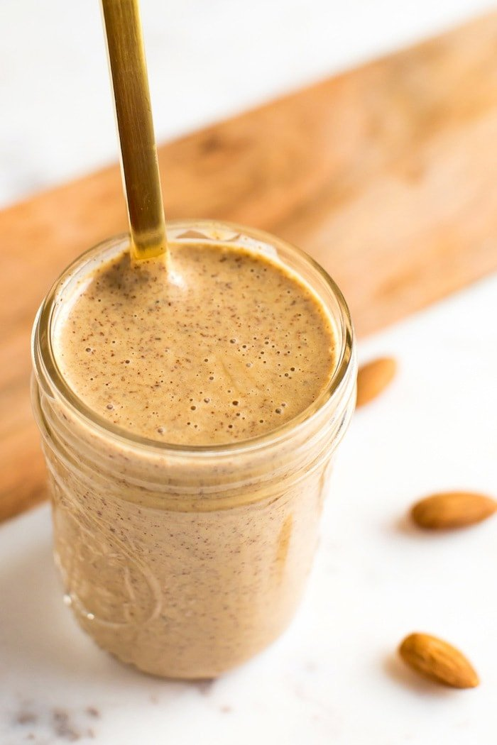 Almond dressing in a mason jar with gold spoon.