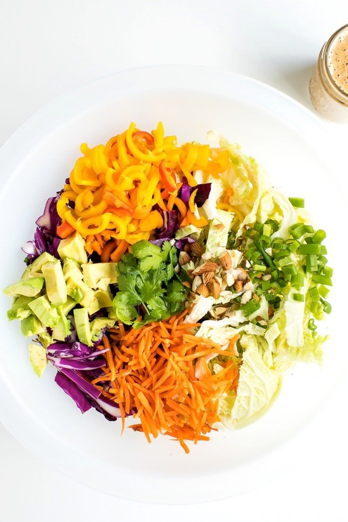 All the ingredients for an Asian chopped salad in a large salad chopper bowl.