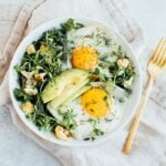 Greens topped with over easy eggs, avocado and roasted cauliflower in a white bowl with a fork on a neutral napkin.