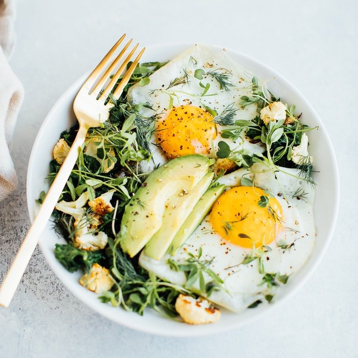 A white bowl with sautéed greens, roasted cauliflower, two sunny side up eggs, avocado, microgreens and fresh dill.