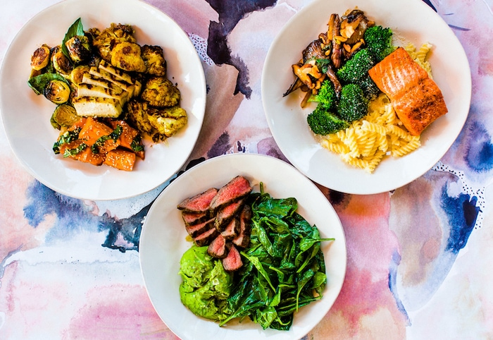 Overhead shot of three plates from Flower Child, a restaurant.