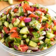 Cucumber, tomato, red onion salad in a glass bowl, next to a cutting board with chopped cucumber and tomato.