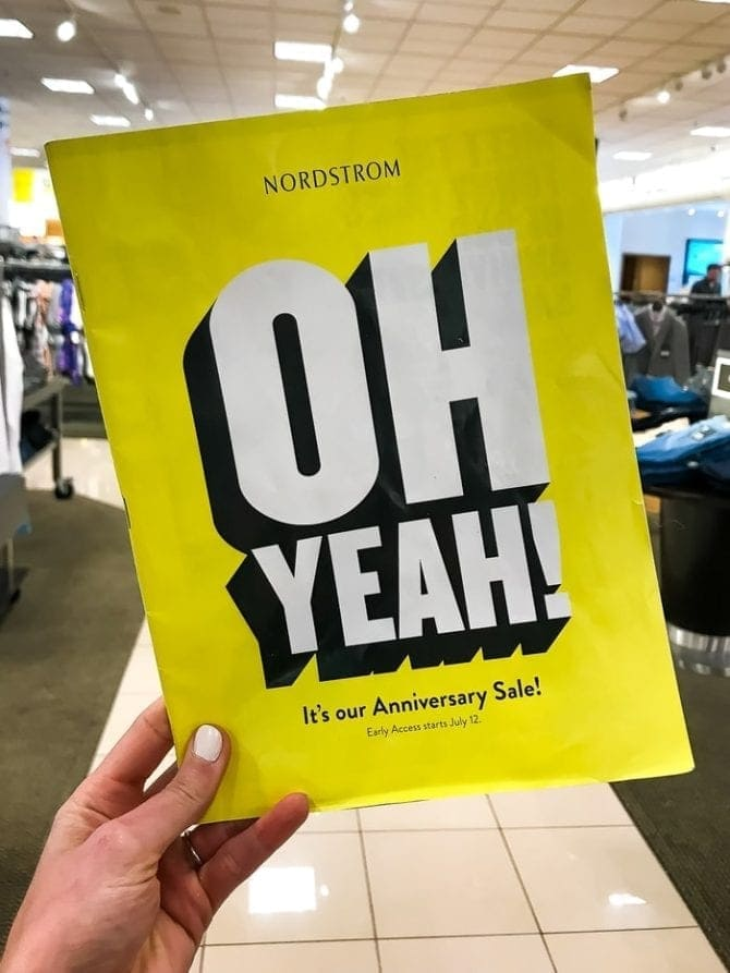 """Woman's hand holding a yellow flyer from Nordstrom's Anniversary sale. The flyer says """"Oh yeah! It's our Anniversary Sale!"""""""