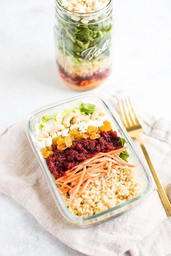 Beet power salad in a meal prep container with quinoa, carrots, beets, raisins, goat cheese, cashews and shredded sprouts on top.