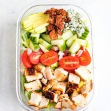 Chicken avocado club salad in a meal prep container.