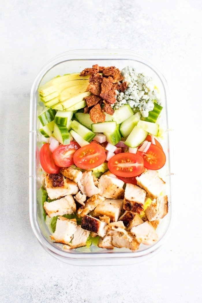 Chicken avocado club salad in a meal prep container.