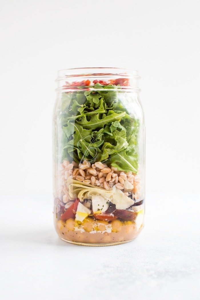 Mason jar salad layered with chickpeas, tomatoes, mozzarella, olives, farro, artichoke hearts, arugula and sun-dried tomatoes.