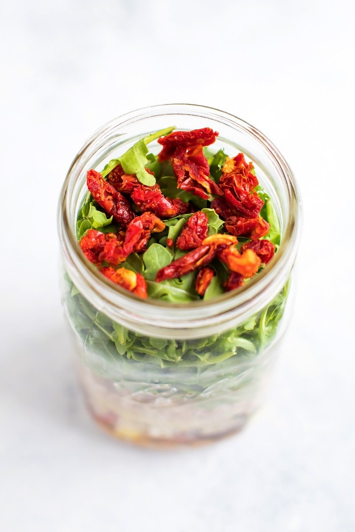 Farro salad in a mason jar, overhead view with sundried tomatoes on top.