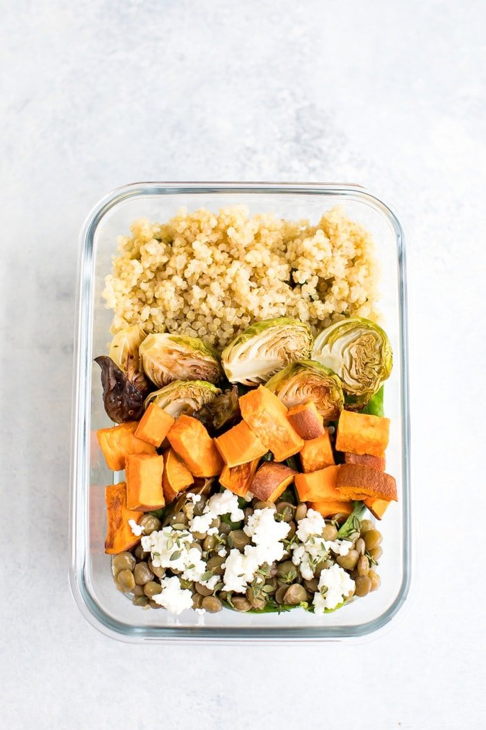 Meal prep salad with red wine vinaigrette quinoa, lentils, roasted brussels sprouts, roasted sweet potatoes, kale and feta.