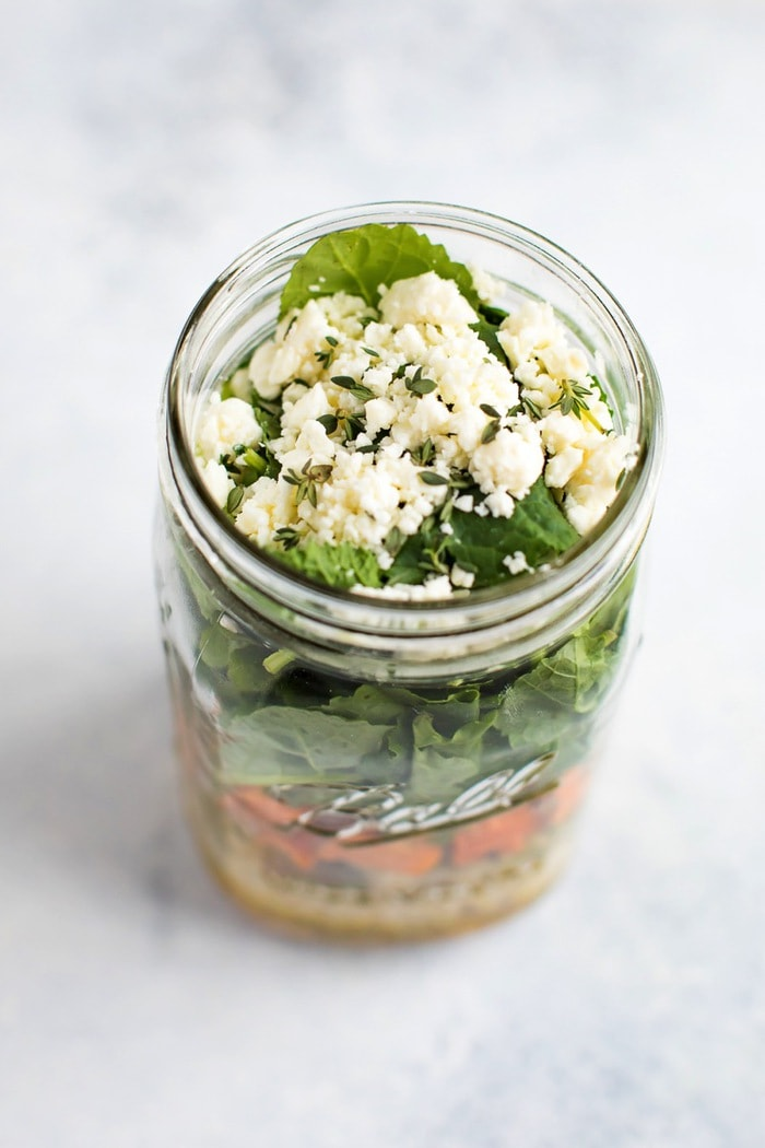 Mason jar salad overhead view with feta and thyme on top.
