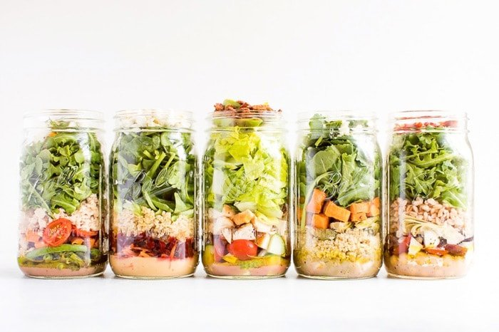 Five different mason jar salads in quart-size mason jars lined up to show off the layers.