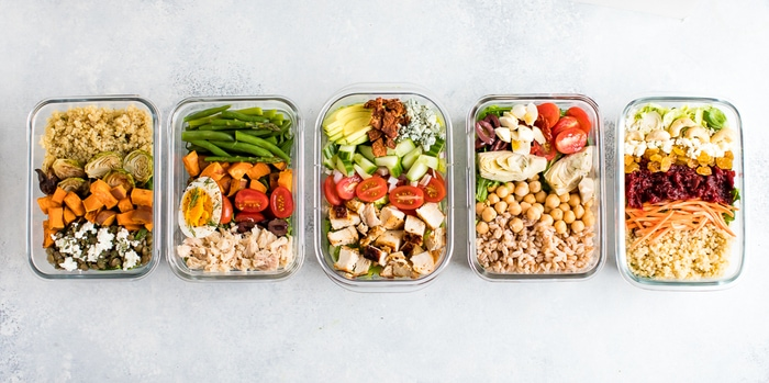 Five different meal prep salads in glass storage containers -- all lined up to show off the layers.