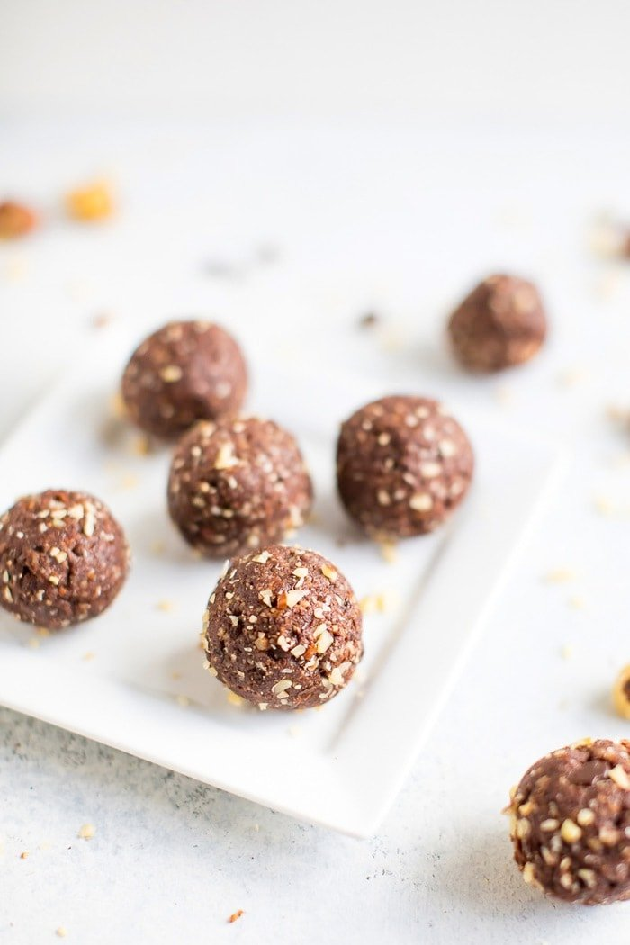 Homemade chocolate hazelnut energy bite in front with additional energy bites in the background on a white plate.
