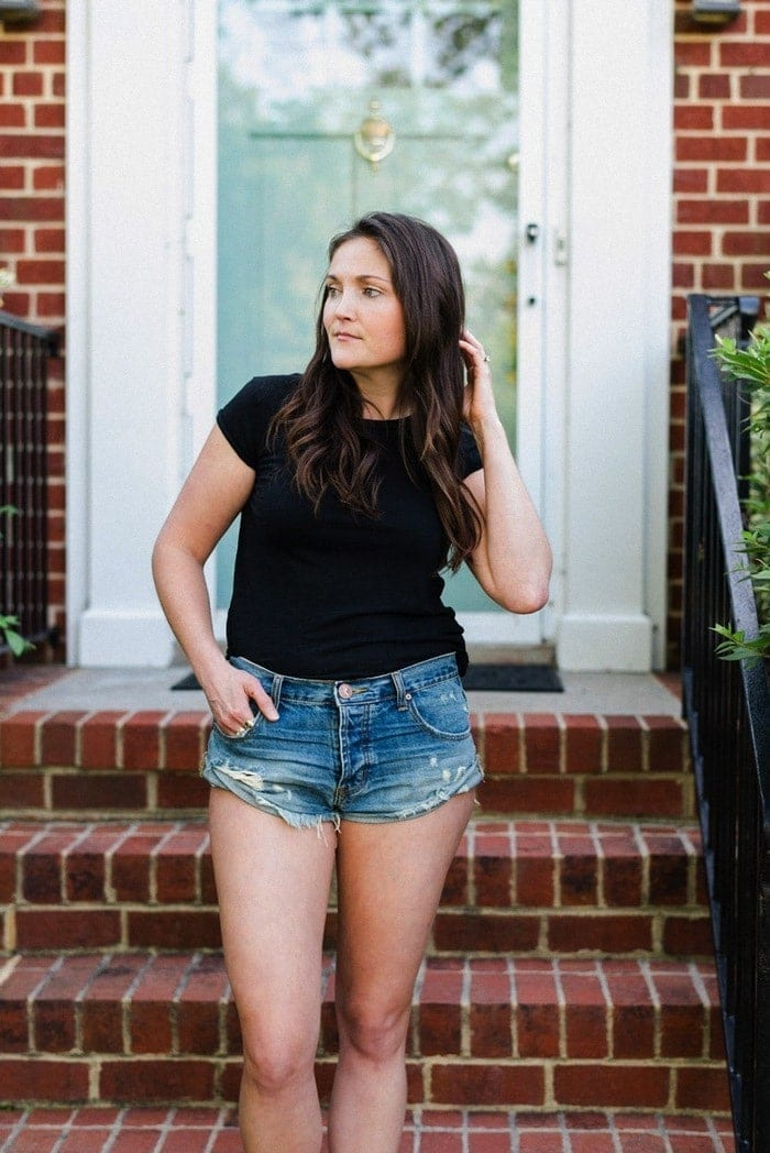 Woman wearing denim shorts and a black tee