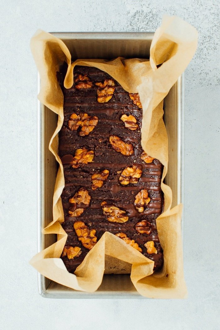 No bake brownies in a loaf pan with parchment. Brownies are topped with walnuts and a chocolate drizzle.