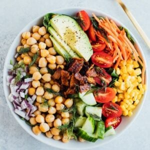 Vegan cobb salad with tempeh bacon and chickpeas in a white bowl with a gold fork.